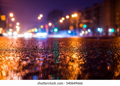 Rainy night in the big city, the car headlights shine through the mist. Close up view from the level of the dividing line