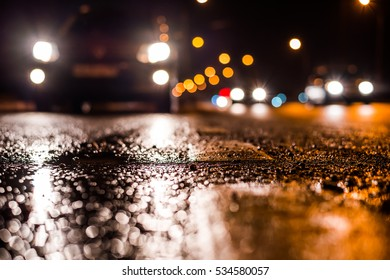Rainy night in the big city, the cars traveling towards the headlights illuminate the road. Close up view from the level of the dividing line - Shutterstock ID 534580057