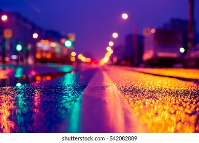 Rainy night in the big city, the empty road with lanterns. Close up view from the level of the dividing line, image in the soft orange-purple toning