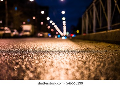 Rainy night in the big city, the empty road. Close up view of a level curb on the road, image in the blue tones