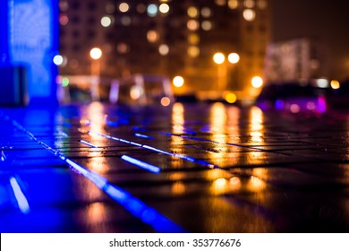 Rainy night in the big city, light from the night club and the windows of the house is reflected in the asphalt. View from the sidewalk level paved with bricks