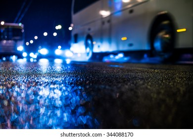 Rainy night in the big city, riding the bus on the road. View from the level of asphalt, in blue tones