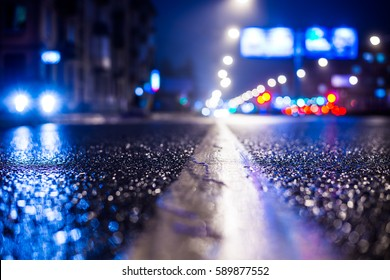 Rainy night in the big city, the road lighting lanterns and headlights of the approaching cars. Close up view from the level of the dividing line, image in the blue tones