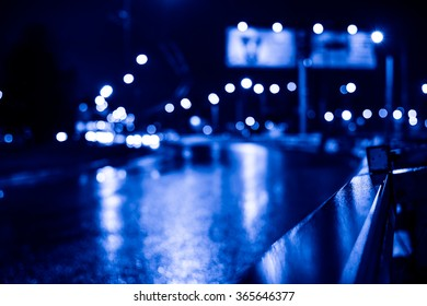 Rainy night in the big city, wet highway after the rain. View of the highway with a dividing border, image in the blue toning