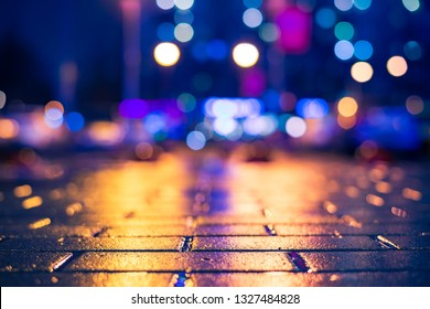 Rainy night in the city. Light from the windows of the house opposite. Car parking. Multi-colored shop windows. Close up view from the pavement level. Orange-blue toning.