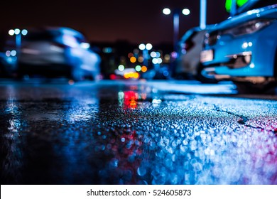 Rainy night in the parking shopping mall, the riding car. Close up view from the asphalt level, image in the blue tones