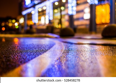 Rainy night in the parking shopping mall, illumination lights are reflected in a asphalt. Close up view from the level of the dividing line
