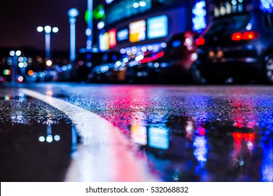 Rainy night in the parking shopping mall, parked cars and marking the line going into the distance. Close up view of a puddle on the level of the dividing line, image in the blue toning