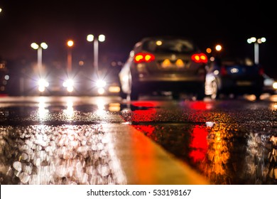 Rainy night in the parking shopping mall, the headlights of the cars. Close up view from the level of the dividing line