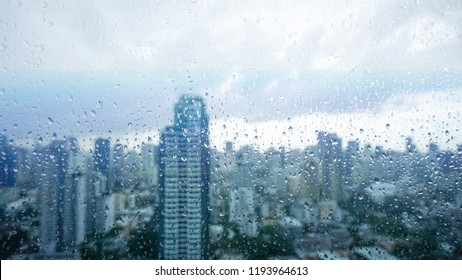 Rainy season, Rain drops on window's glass is viewing the downtown city skyline on a dark weather day. Abstract rain drop/raining scenery background - can be used for display or montage your products.