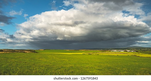 Rainy sky above the green field. Northern Ireland panoramic view. Breathtaking landscape the huge white clouds, grass covered meadow before the rain. Picturesque Irish countryside background.