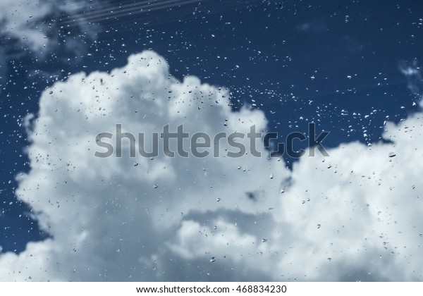 Rainy sky with white clouds, and raindrops on the window