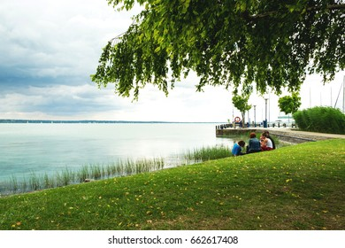 The rainy summer scenery of the famous spa resort of Hungary - Lake Balaton - the rocky coast, the clean water with reflection and a quiet and relaxing family picnic on the green meadow in Tihanj