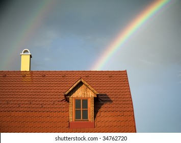 Rainy weather, clouds, rainbow, and a wet roof of a house.