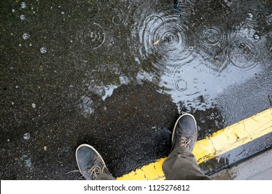 Rainy weather. Male legs in sneakers or boots walking through the rain puddle on the asphalt road, top view. Film grain photo.