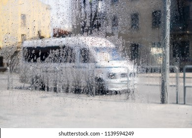 Rainy weather on a city street. Drops of water flow down the windowpane. The traffic of cars along the road.