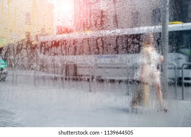 Rainy weather outside the busy street. The bus and the pedestrian are moving in the rain. Drops of water on a glass window. Abstract background