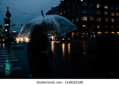 rainy weather people with umbrellas stand at a traffic light