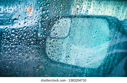 Rainy weather, raindrops on the car. Photo taken from inside of the car and outside