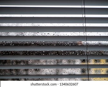 Rainy weather: Wet window with raindrops and grey sky, houses out of focus in background