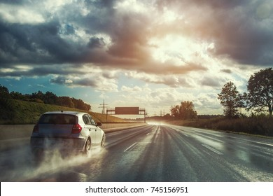 rainy wet highway with car in fog water spray
