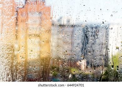 Rainy window Window with drops Window after rain Blurred buildings Sunny Sun after rain