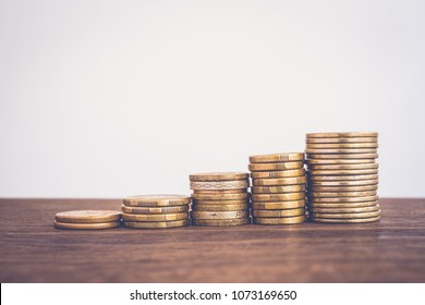 Raise gold coin stacks, worldwide currency on wooden table Blank background copy space, vintage style. Money concepts for saving, growth fund, increase invesment, finance, business budget planning.