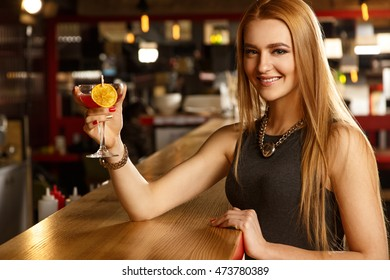 Raise your glass. Portrait of a beautiful cheerful young woman smiling to the camera raising her glass at the bar
