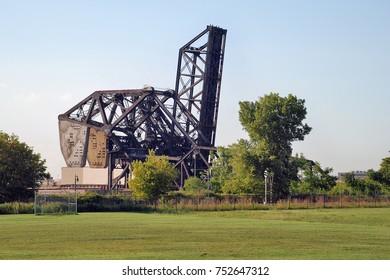 Raised bascule railroad bridge in Chicago over a grassy field