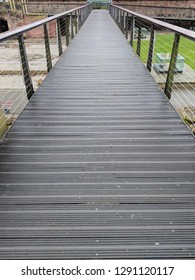Raised boardwalk footbridge with handrails either side, disappearing to it's vanishing point
