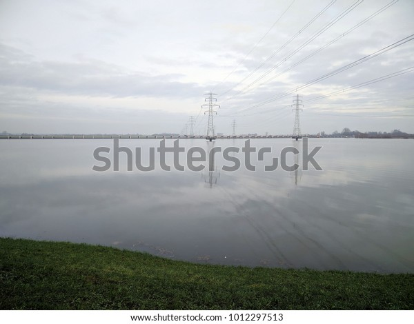 raised electricity poles above water surface at Tolbrug, a movable inlet across the high water channel, part of the national flood protection programme. VEESSEN, THE NETHERLANDS - JANUARY 7, 2018