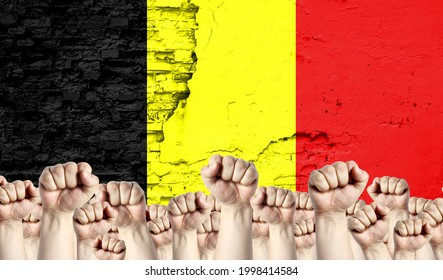 Raised fists of men against the background of the flag of Belgium painted on the wall, the concept of popular unity and the opinion of the majority.
