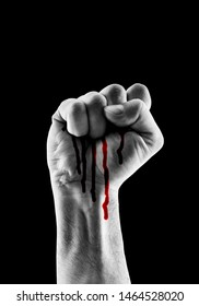Raised hand showing fist with red blood isolated on black background