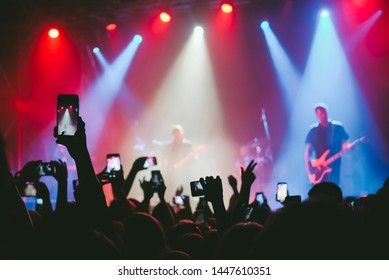 Raised up hands with cellphones recording videos from music show