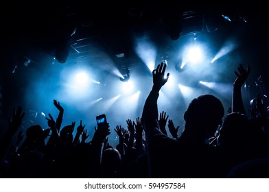 Raised hands of fans during a concert (show or performance) on the background of blue rays of light