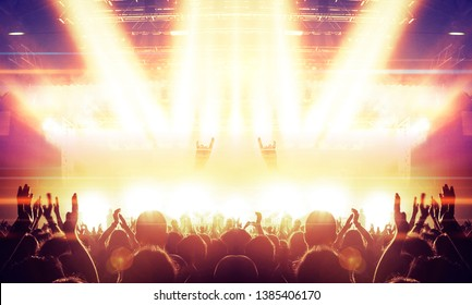 Raised hands in front of a concert stage for a festive crowd