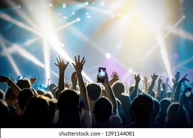 Raised hands in honor of a musical show on stage, People in the hall