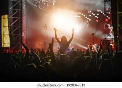 Raised hands in honor of a musical show on stage, People in the hall - Shutterstock ID 1928347313