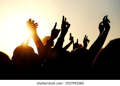 Raised hands of many people at a big mass event.