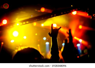 Raised hands of many people at a big public event.