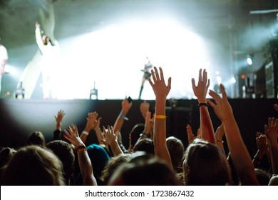 Сrowd with raised hands at music festival. Fans enjoying rock concert with light show and clapping hands.
