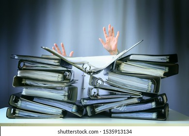 raised hands of a person who sinks behind stacks of ring binders on an office desk, concept of excessive demands and increasing work in business, selected focus