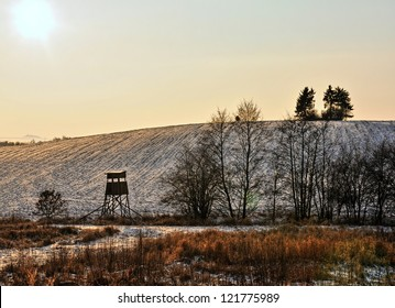 Raised hide at sunset in the field when the big freeze