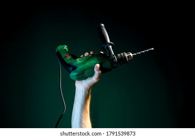 A raised Male hand holds a drill on a dark green background
