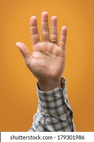 Raised Male Hand Isolated on Yellow Gold Orange With Blue Plaid Shirt and Wedding Ring