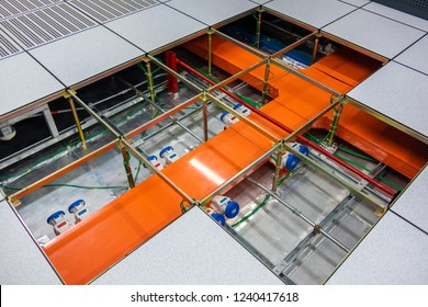 Raised under floor air system and suction tool in modern interior of server room in data center. Network wires in the floor, which can be seen through the open hatch. Undergoing renovations.