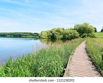 A raised wooden walkway runs at the side of Staunton Harold reservoir, towards the distant fields.