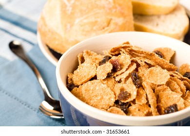 Raisin bran cereal accompanied by bread and butter
