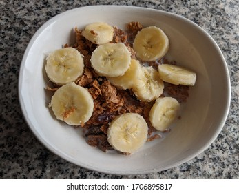 Raisin & Bran Cereal with Sliced Yellow Bananas in a White Ceramic Bowl with Milk on a Granite Table for a Healthy Breakfast