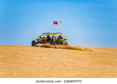 Raising a cloud of sand and dust.Off Road Dune Buggy riding a sand dune in the Imperial Sand Dunes recreation area.California 19 January 2018